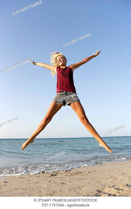 Healthy young woman jumping for joy on the beach
