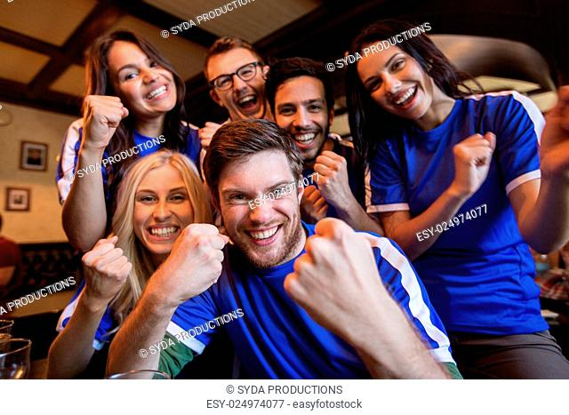 sport, people, leisure, friendship and entertainment concept - happy football fans or friends drinking beer and celebrating victory at bar or pub