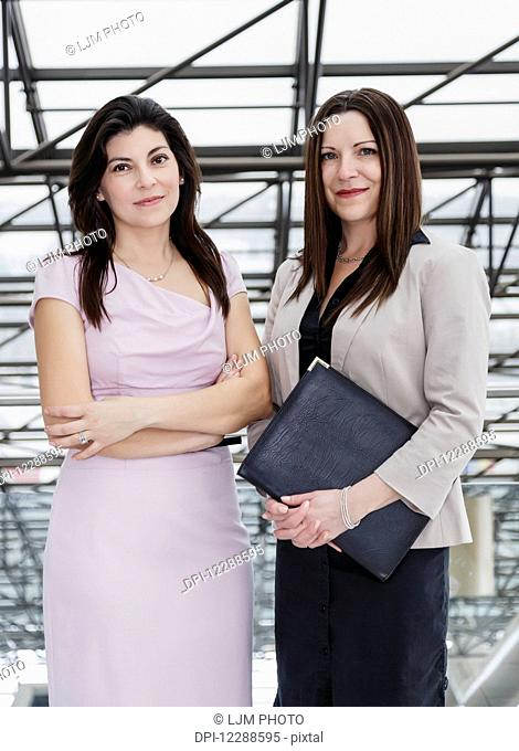 Two professional business women in the atrium of an office building; Edmonton, Alberta, Canada