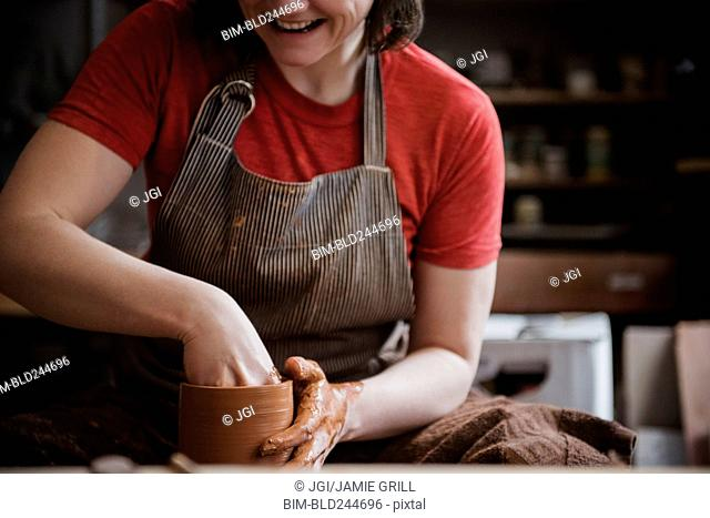 Caucasian woman shaping pottery clay