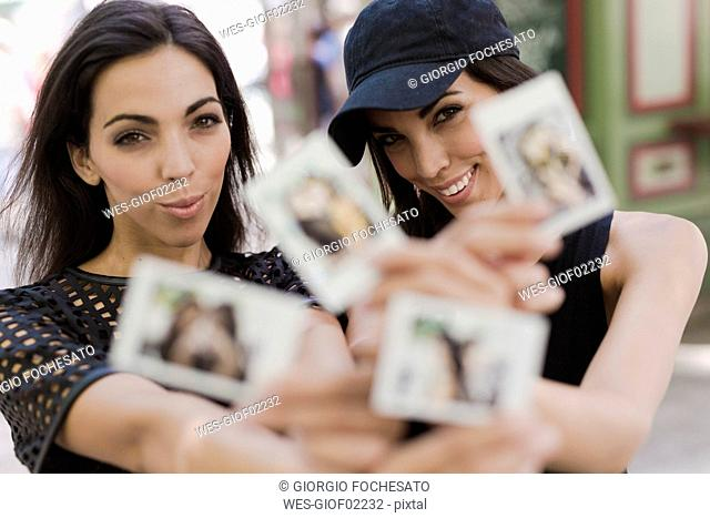Two happy twin sisters holding instant photos