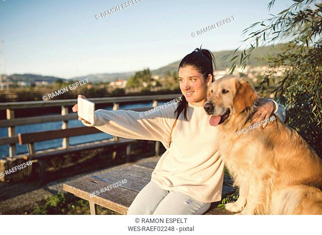 Smiling young woman taking a selfie with her dog at the waterfront