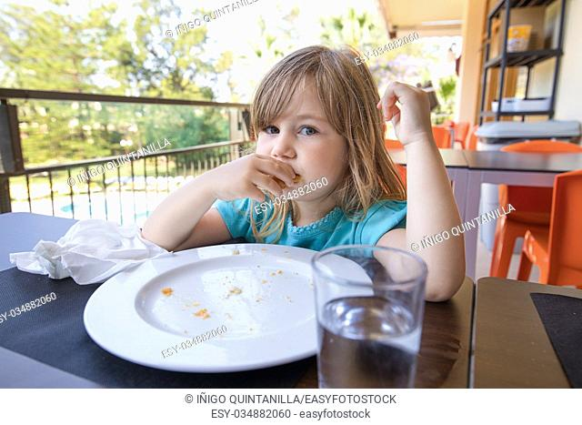 portrait of blonde caucasian child three years old with blue shirt, at breakfast, looking and eating, with no food on dish, only crumbs on the plate