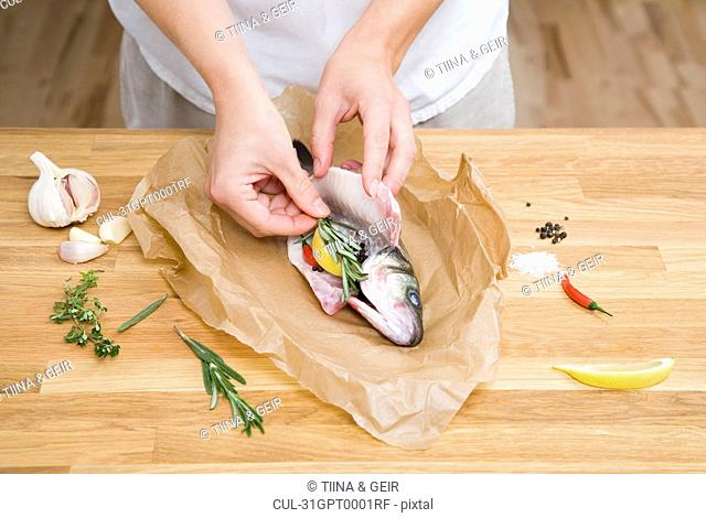 Preparing fish with herbs, spices, lemon
