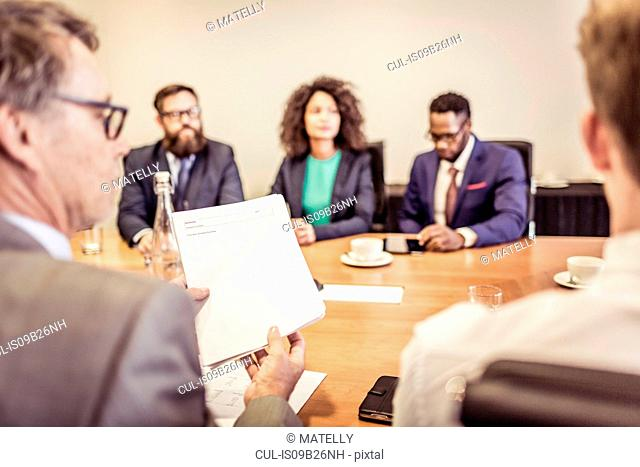 Over the shoulder view of businesswomen and men at conference table meeting