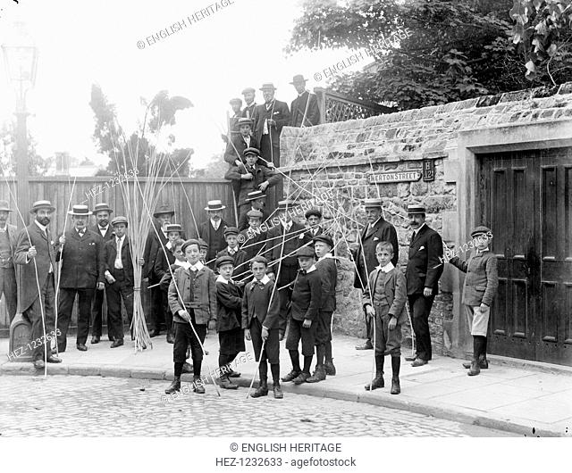 Beating the Bounds ceremony, Merton Street, Oxford, Oxfordshire, 1908. A group of children and other parish people in the street holding willow sticks taking...