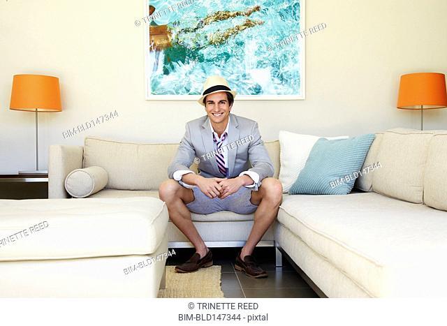 Trendy Caucasian man sitting in modern living room