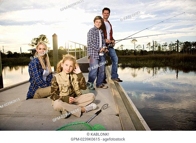 Portrait of young happy family fishing by river