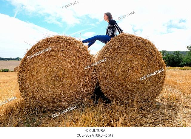 Young woman sitting on top of haystacks in harvested field