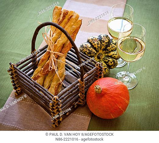 basket with parmesan cheese twists puff pastry cheese straws and wine