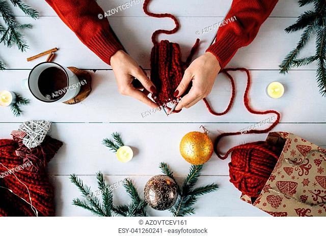 The woman knits Christmas things on white wooden background. Christmas composition