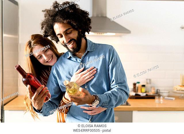 Couple standing in kitchen, preparing dinner party, choosing wine