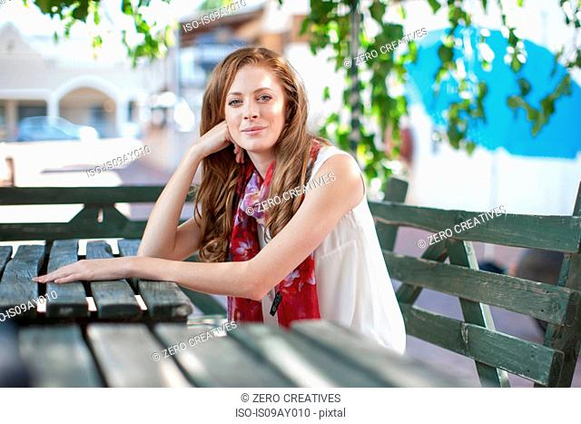 Portrait of young woman in city at sidewalk cafe