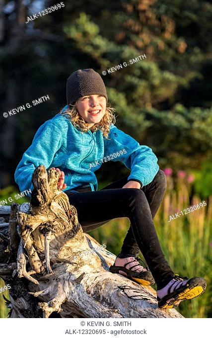 Young girl sitting on driftwood along the beach, Seldovia, Southcentral Alaska, USA