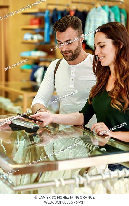 Couple in a boutique paying with smartphone