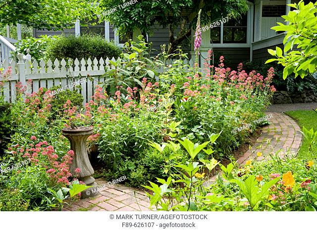 Small sundial framed by Jupiter's Beard, bordered by curving brick path (Centranthus ruber). Jepson, Bellingham, WA