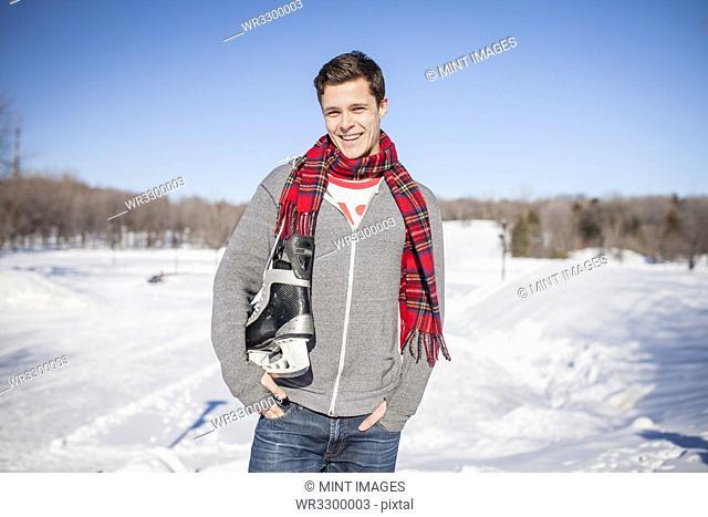 Caucasian man carrying ice skates in snow
