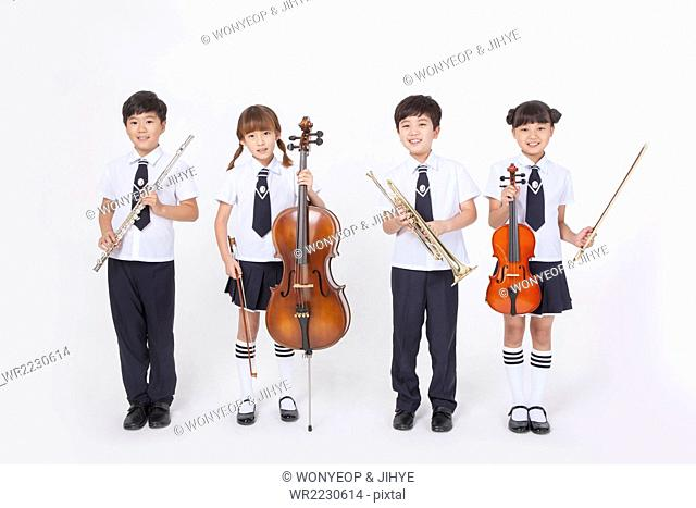 Four elementary school students in school uniforms standing with a classical musical instrument each