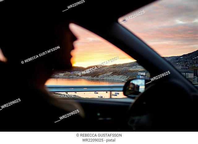 Young man driving car with sea view seen through window