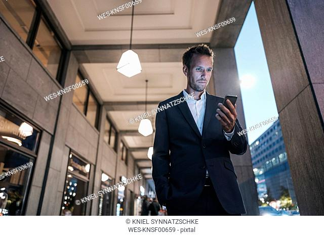 Germany, Berlin, portrait of businessman looking at his cell phone