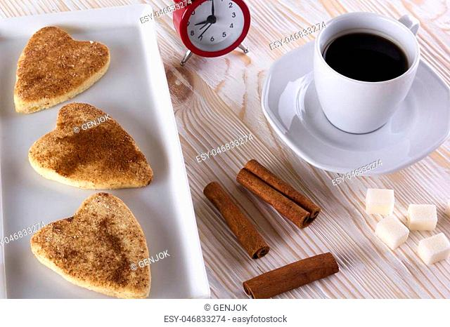 Cup of coffee with cinnamon cookies on wooden background
