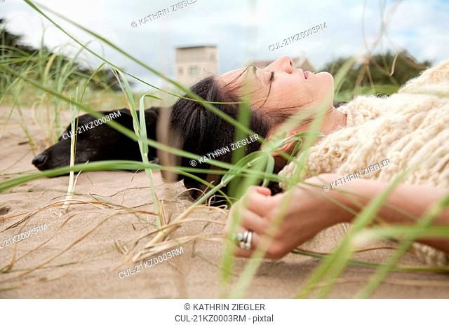 Woman and dog lying in the dunes