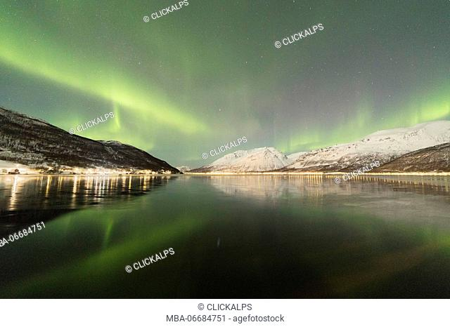 The Northern Lights is reflected in the icy sea surrounded by snowy peaks Manndalen Kafjord Lyngen Alps Tromsø Norway Europe