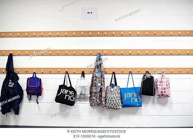 Bags hanging up on coat hooks in a secondary school cloakroom, UK
