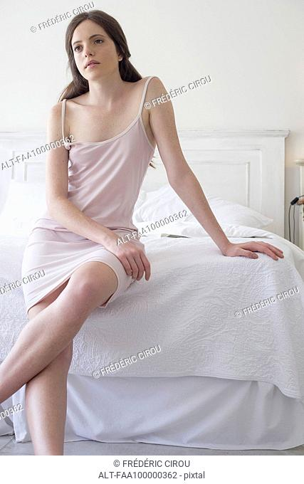 Woman sitting on edge of bed