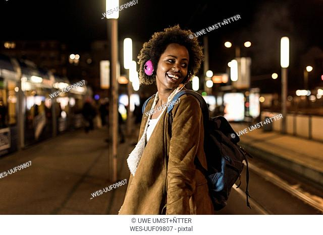 Smiling young woman with headphones and backpack waiting at the tram stop
