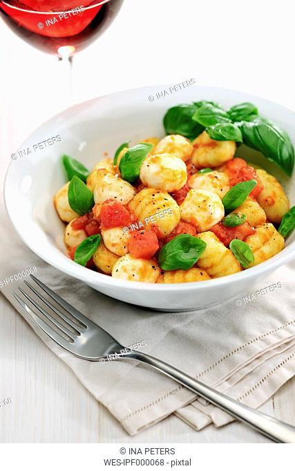 Bowl of gnocchi with tomato sauce, mozzarella balls and basil