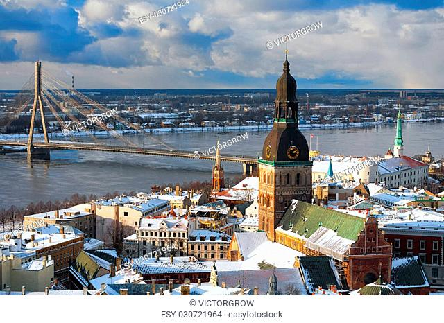 Roofs of houses and cathedral spiers of Riga bridge on the river from the air in winter