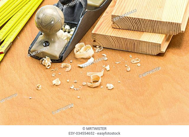 Carpenter's plane and folding rule with shaving on wooden background