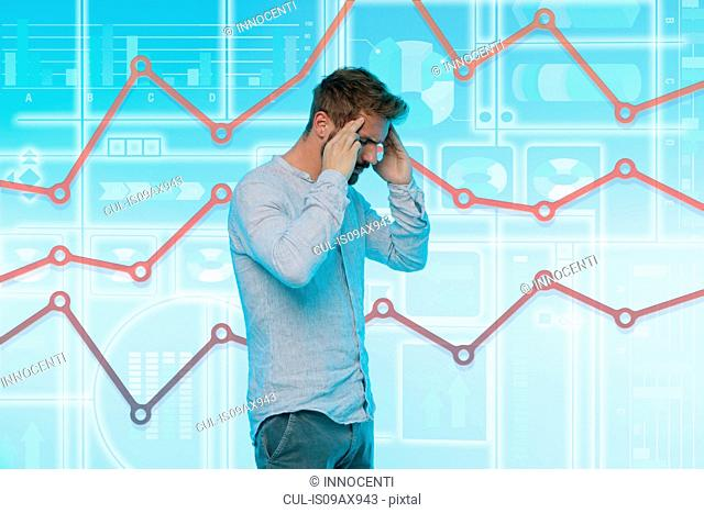 Man touching temples, stressed expression, graphical screen with data behind him