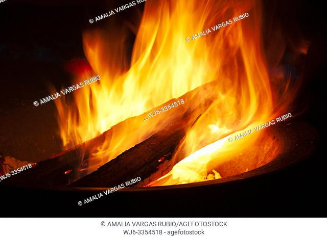 Approaching logs burning between the flames to fan the fire that illuminates a black night