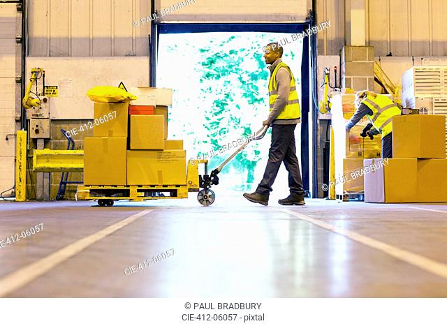 Worker carting boxes in warehouse