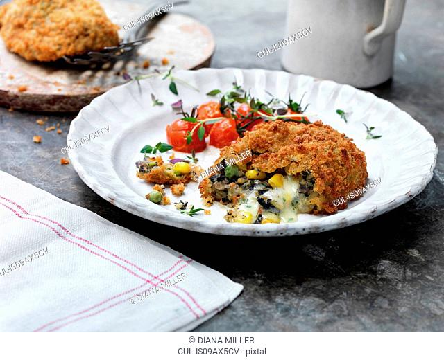 Vegetarian kiev on plate with tomatoes