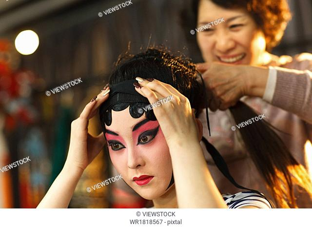 The stylist for the Peking Opera actors doing hair style