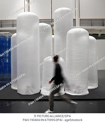 """03 April 2019, Baden-Wrttemberg, Karlsruhe: At the Center for Art and Media (ZKM) a person passes by Yasuaki Onishi's installation """"""""Vertical Volume ACG"""""""" from..."""