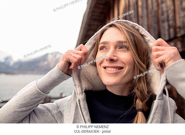 Mid adult woman outdoors, wearing hooded sweatshirt, pulling hood up