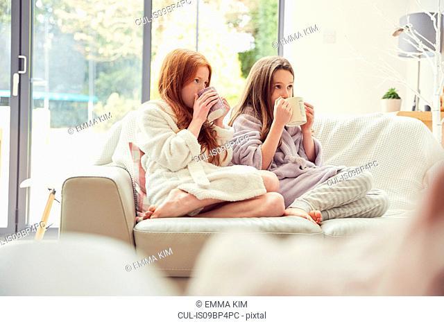 Girls having warm drink on sofa