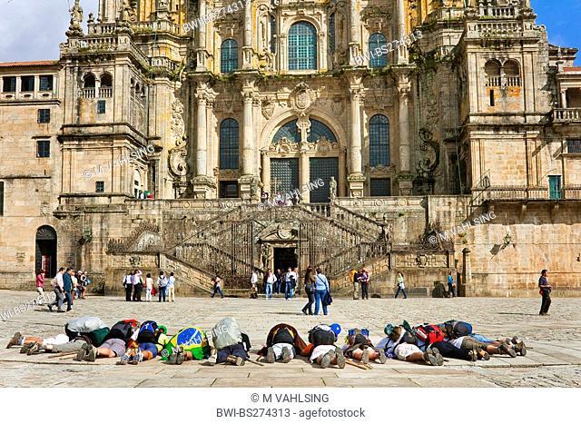 Brasilian pilgrims lying on the grpund and praying in front of the cathedral on Praza do Obradoiro, Spain, Galicia, Corua, Santiago De Compostela