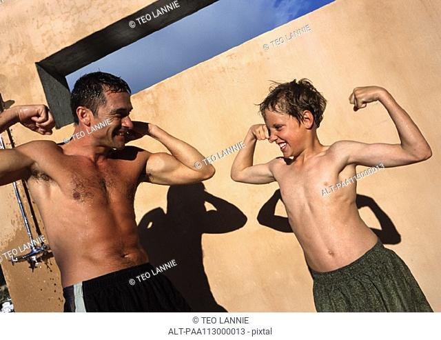 Man and boy flexing arm muscles, making faces