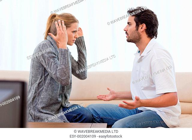 Young couple arguing in their living room