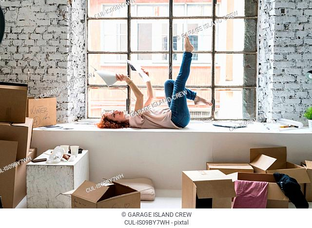 Mid adult woman moving into industrial style apartment, lying on window ledge looking at photographs