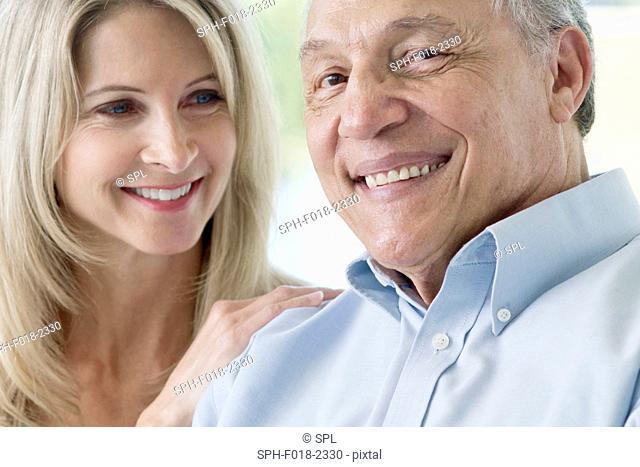 Senior man and mature woman smiling towards camera