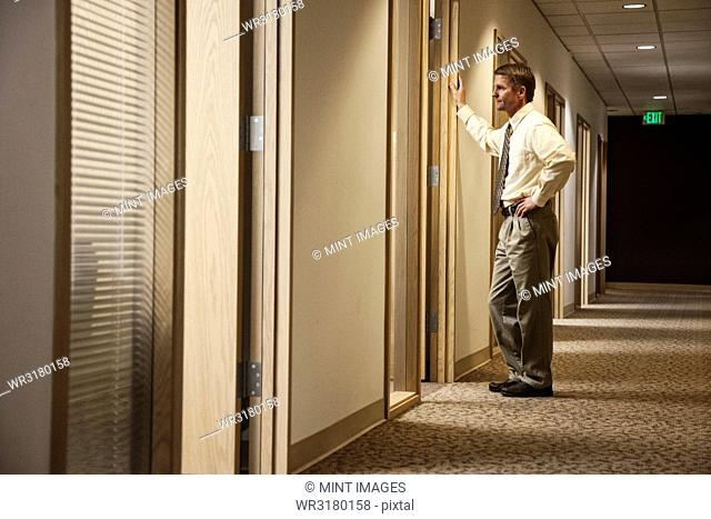 Caucasian man a hallway meeting with another person in an office
