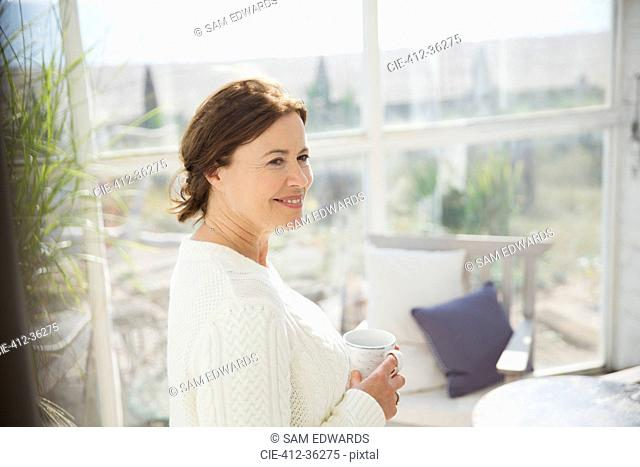Smiling mature woman drinking coffee on sunny beach house sun porch