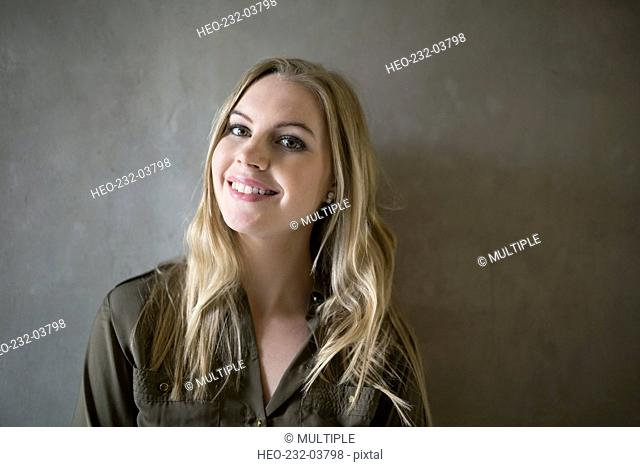 Portrait smiling blonde businesswoman against gray background