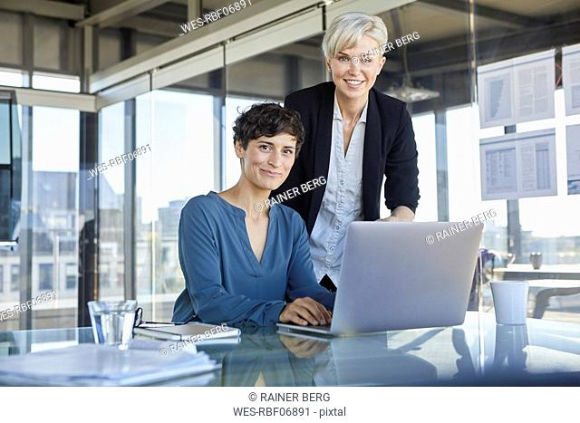 Portrait of two smiling businesswomen with laptop at desk in office